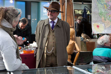 untidiness: London - January 17, 2015. well-dressed salesman hat talking with shoppers. Flea market with old-fashioned goods displayed in London city, UK. On 17 January 2015. Editorial
