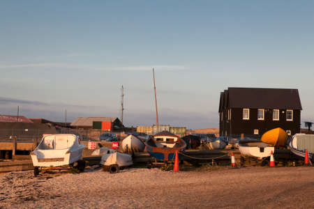 dockside: WHITSTABLE, UK - AUGUST 21 2015: Fishing boats and nets made from plastic bottles in Whitstable harbour. Visitors to can also be seen on the dockside. The harbour was built in 1832.