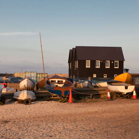 WHITSTABLE, UK - AUGUST 21 2015: Fishing boats and nets made from plastic bottles in Whitstable harbour. Visitors to can also be seen on the dockside. The harbour was built in 1832.