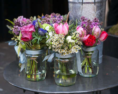 aspidistra: Small bouquets of lilacs, hyacinths, anemones, roses and peonies in small glass jars on an iron table. Stock Photo