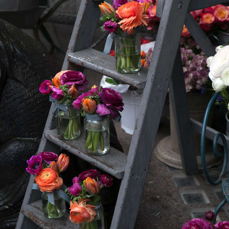 mixed marriage: Spring bouquet with purple  ranunculus, orange tulips and anemones in a glass jar on the stairs Stock Photo