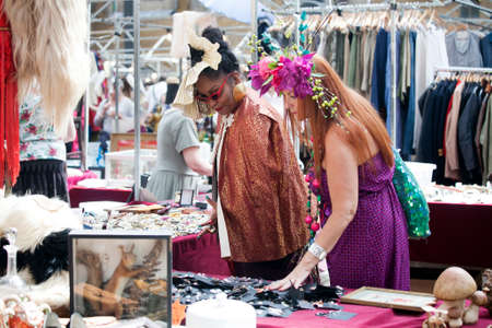 antiques: London, UK - July 1, 2016: Customers looking at antiques at a stall in Brick Lane, Whitechapel. On Sunday Brick Lane is home to one of the most popular street markets in the Capital
