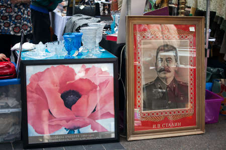 hamlets: LONDON-JUNE 27:Shoppers at Spitalfields Antic Market June 27,2016 in London. Market is fourth most popular attraction in city attracting over 100,000 people each weekend.  Portrait Stalin and Picture of poppy for sell