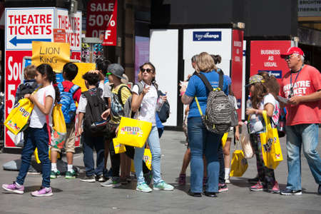 ms: London, UK - July 17, 2016. happy shoppers with yellow packets M & MS Chocolate Candy