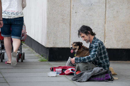 poor man: London, UK - July 17, 2016. a poor man with a dog begging on the street.