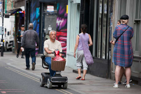 incapacitated: London, UK - July 17, 2016. Elderly man drive mobility scooter. Editorial