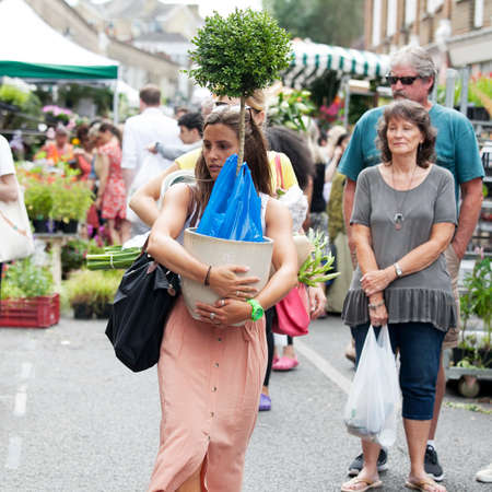 sunday market: London, UK - July 17, 2016. Woman carrying a flower that bought at the Columbia flower market Editorial