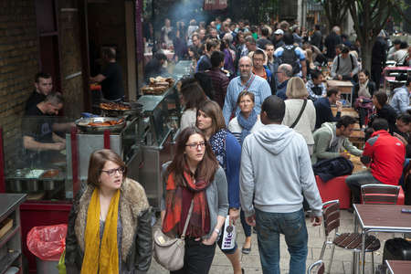 hectic life: London, England - August 20, 2015: People walk by whilst someone is selling food at stall in Borough Market, London. A market has traded in Southwark, London for more than 250 years