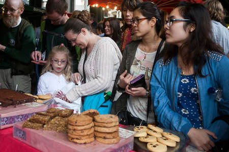 hectic life: London, England - August 20, 2015: People walk by whilst someone is being served by staff at a bakery stall in Borough Market, London. A market has traded in Southwark, London for more than 250 years