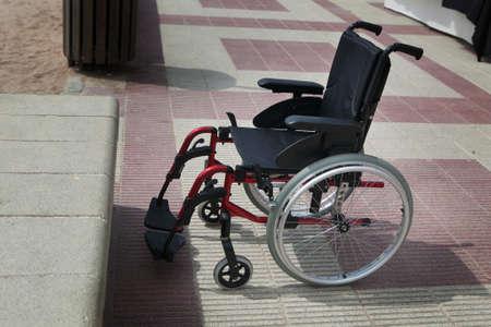 Empty wheelchair on a beach near beach