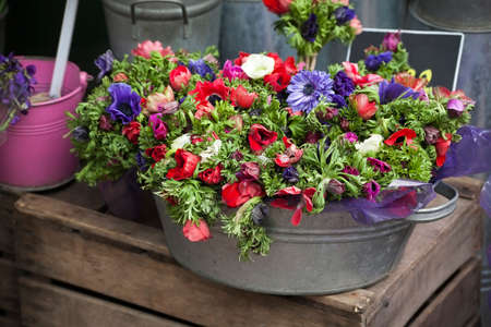 Flower for sale. red and purple anemone in zink bucket on the wooden box