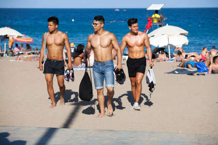 beach hunk: JUNE 18, 2016 - BARCELONA, SPAIN: Unidentified Well-built men in shorts are on the beach at Barcelona city