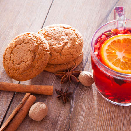 A glass of hot mulled wine with apple,orange and spices on a background of traditional Christmas decorations.