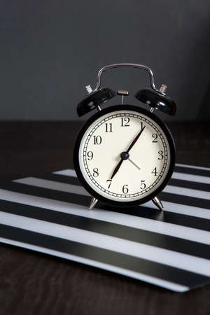 pm: the Black alarm clock on a black and white striped napkin showing 7 oclock on a bedside table