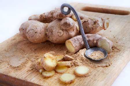 Close up of different forms of ginger against a wood worktop