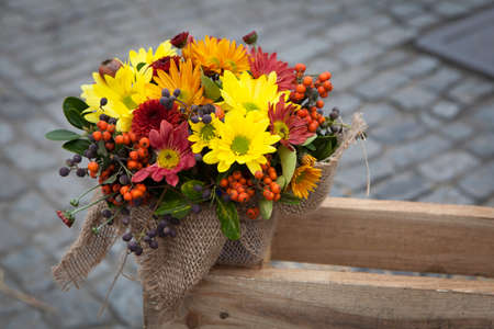 Autumn bouquet of yellow, orange, brown carnations with eucalyptus in a vase wrapped by canvas as decoration street market