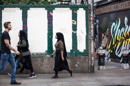 hamlets: LONDON, UK - August 27, 2016: Asian people walking on the street Brick Lane, London, England Editorial