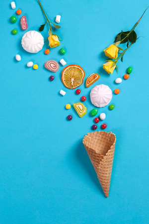 liquorice: Marshmallows, candy, jelly beans, sweets , dry mugs oranges and yellow roses falling in wafer cone on a blue background. Copy space