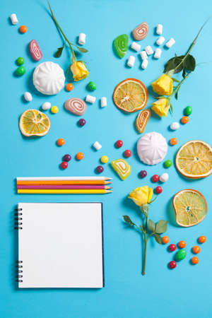 liquorice: Marshmallows, candy, jelly beans, sweets , dry mugs oranges and yellow roses falling on a notepad on a blue background. Advertising Space Stock Photo