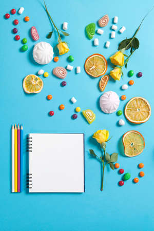 advertising space: Marshmallows, candy, jelly beans, sweets , dry mugs oranges and yellow roses falling on a notepad on a blue background. Advertising Space Stock Photo