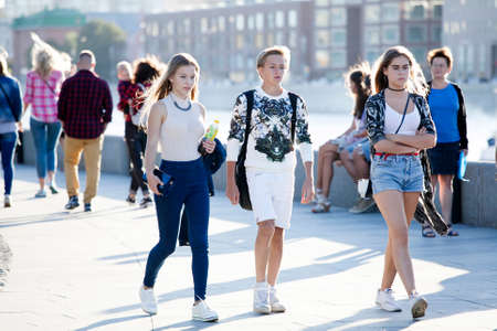 diversidad cultural: Moscow, RUSSIA - June 23, 2016: Cultural diversity in Moscowy - teens walking the waterfront promenade in sunsetting light Editorial