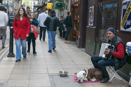 harmonist: LONDON - August 27, 2016: Street musician playing the accordion, with the dog Editorial