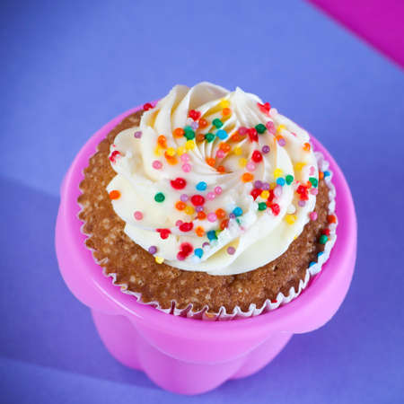 sugarpaste: Cupcakes with white cream on the pink and blue background, arranged for a party or a wedding reception