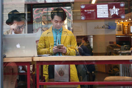 KING'S CROSS, LONDON, UK - JULY 21, 2016. Local people enjoying the cafe culture of King's Cross in London whilst drinking coffee and reading in Pret cafe. Two fashionable young man in a yellow raincoat. One of them works at a computer, other checks the p Editorial