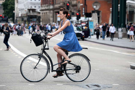 LONDON, UK - August 27, 2016: serious girl in a blue dress with polka dots crossing the road on a bicycle