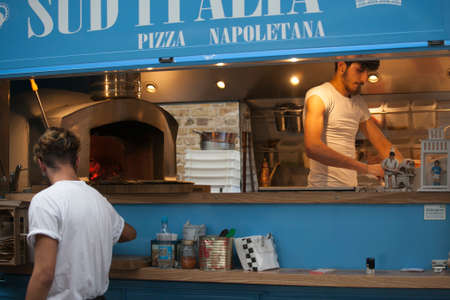 LONDON, UK - August 27, 2016: a young man making a pizza in a mobile cafe
