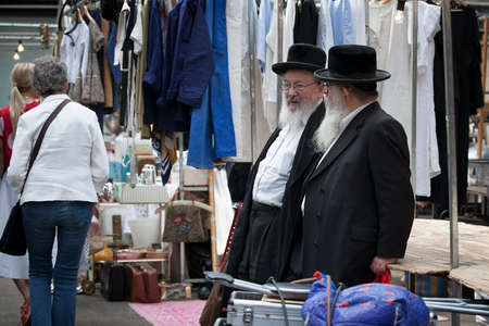 LONDON, UK - August 27, 2016: Two elderly Orthodox Jewish men with beards wearing black coats and hats chatting on Spitalfilds market Editorial