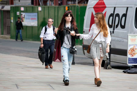 ttractive: LONDON, UK - August 27, 2016: Two hipster girls dressed in cool Londoner style walking in Brick lane, a street popular among young trendy people