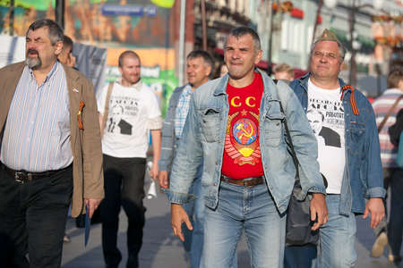 MOSCOW,RUSSIA - MAY 9,2016: May 9,Russia celebrates victory over Nazi Germany,while remembering those who died. men in T-shirts with symbols of the Soviet Union are on the street