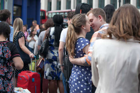 LONDON, ENGLAND - JULY 12, 2016 Young loving couple embracing and kissing at rush hour near the metro Covent Garden Editorial