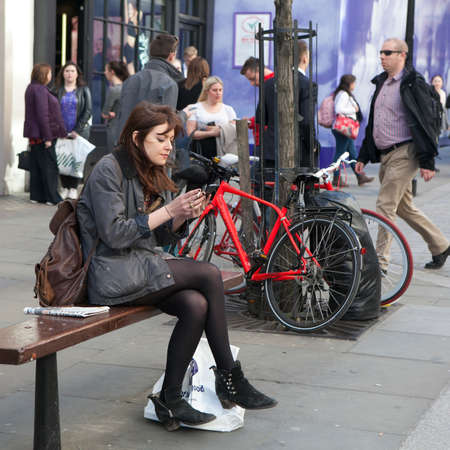 LONDON, ENGLAND - JULY 12, 2016 serious girl with long hair sitting on a bench near Covent Garden