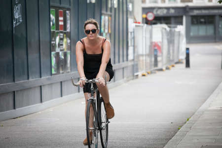 LONDON, UK - August 27, 2016: serious girl in a black dress crossing the road on a bicycle Editorial