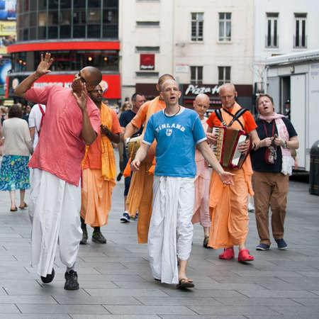 anachronistic: London, UK - July 17, 2016. Hare Krishna followers walk down Londons Oxford Street in their orange robes