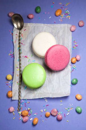 liquorice: the macaroons are with candy and spoon at white napkin at blue background, sprinkled with sugar Stock Photo