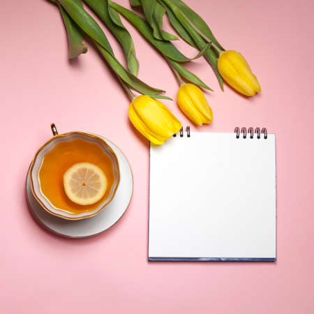 the Yellow tulips with notebook and cup of tea on a pink background