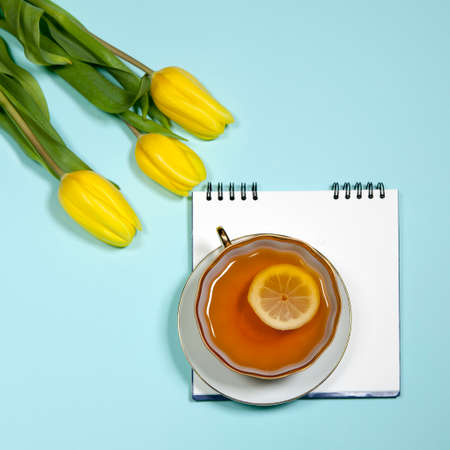 the Yellow tulips with notebook and cup of tea blue background