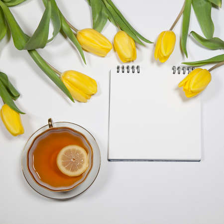 the Yellow tulips with notebook and cup of tea on a white background