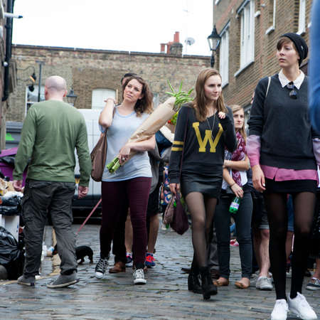 wine road: LONDON, ENGLAND - JULY 12, 2016 Sunday flower Columbia road flower market. The local going for flower, sitting on sidewalks, drink wine, eat and listen to the street musicians. Some of them dancing.