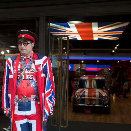 britannia: LONDON, ENGLAND - April 12, 2016 Seller wears uniform symbolizing English flag at entrance of shop Cool Britannia. In background car painted in color of British flag. Editorial