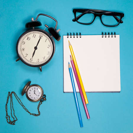 Clock, white notebook on springs, glasses and colored pencils on a blue background. Copyspace