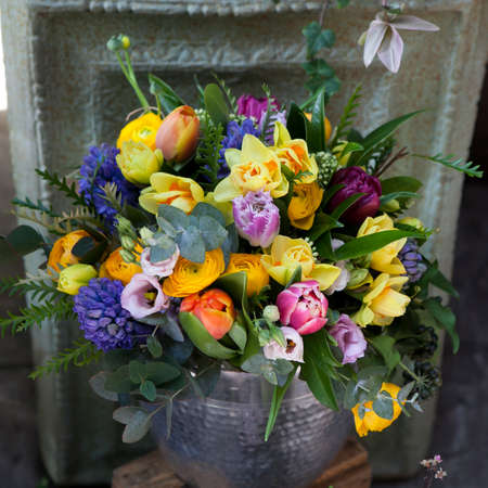 hyacinths: Bouquet of yellow tulips, blue hyacinths, eucalyptus and ranunculus in metal vase