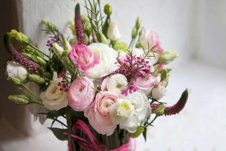 Spring bouquet of pink Ranunculus, lisianthus and Veronica for a special wedding ceremony. Copy space Stock Photo