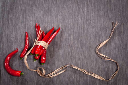Postcards for recipes. Red chile pepper, tied with twine, on a gray napkin. Copy space