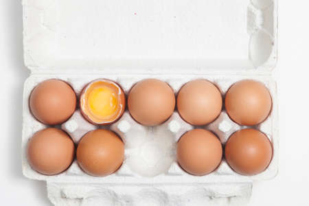 foodstill: A broken egg among whole eggs in an egg carton