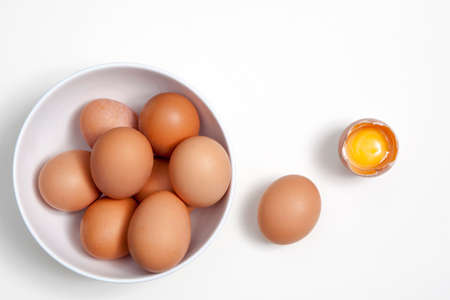 Eggs in a white plate, one whole egg next to broken egg on the table on the white background Stock Photo