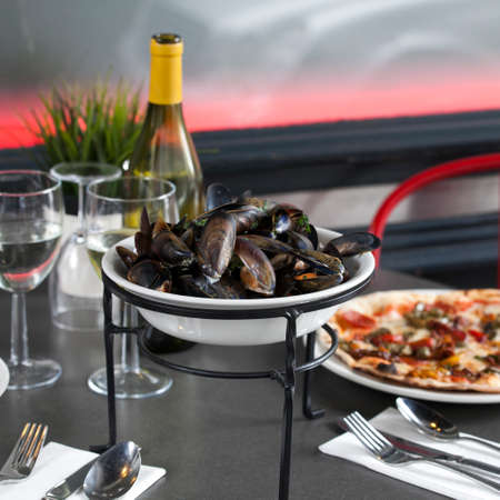 white wine: A bottle of white dry wine, oysters and pizza. Covered table for the reception of guests Stock Photo